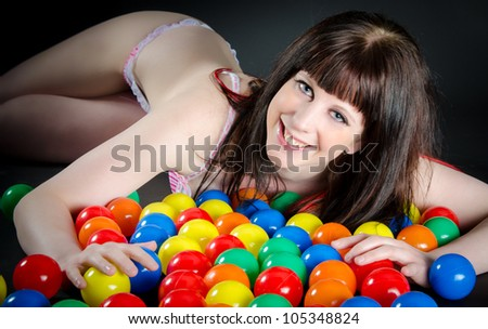 Smiling woman in underwear lying on colorful balls