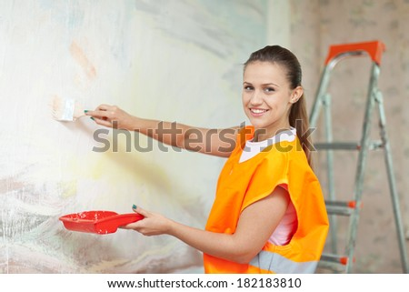 Smiling woman in uniform paints wall with brush