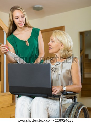 Smiling woman in wheelchair answering on questions of female clerk - stock photo