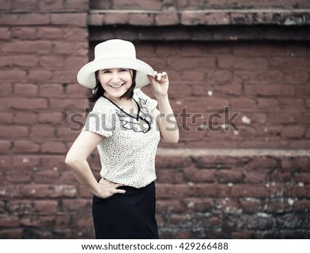 Smiling woman in white hat posing against brick wall background. Selective focus on woman. Toned photo with copy space. Vintage style photo. - stock photo