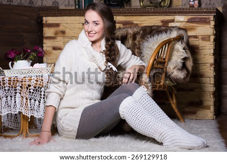 Smiling woman in white stockings and blouse sitting on the carpet - stock photo