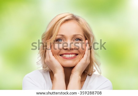 smiling woman in white t-shirt touching her face - stock photo