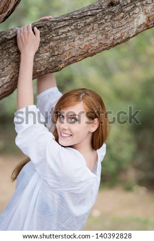 Smiling woman in woodland standing with her arms raised and hands around the branch of a tree - stock photo