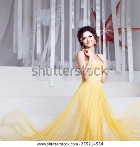 smiling woman in yellow evening dress and with beautiful hairstyle, party - stock photo