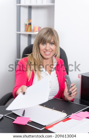 Smiling Woman is handing over a document in direction camera while sitting at the desk in the office. She holds a phone in the other hand. The woman is looking to the camera.
