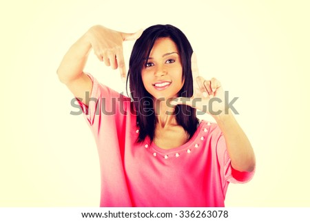 Smiling woman  is showing frame by hands. Happy girl with face in frame of palms. - stock photo
