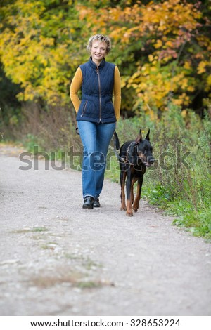 Smiling woman is walking with dobermann in a park. - stock photo