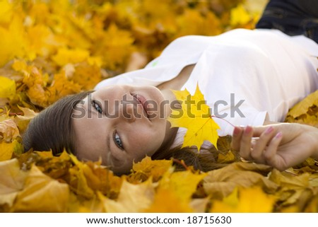 smiling woman laying on falling leaves