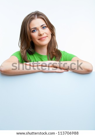 Smiling woman leaning on big blank board . Close up female face portrait with arms on blank card.