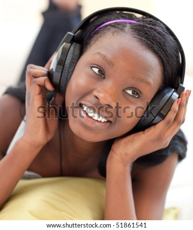 Smiling woman listening music with headphones lying on a sofa