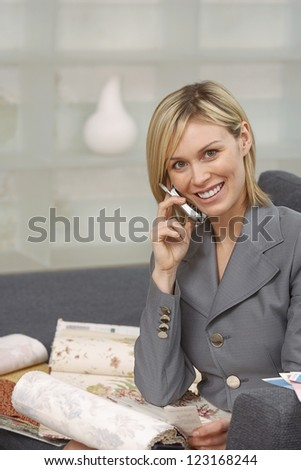 Smiling woman listening to her mobile phone while she looks through fabric sample books - stock photo