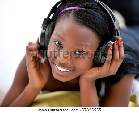 Smiling woman listening to music and lying on sofa - stock photo