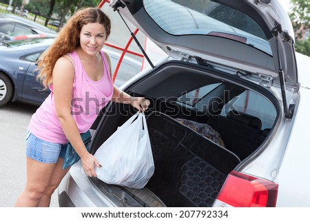 Smiling woman loading shopping bag in trunk of her pov - stock photo