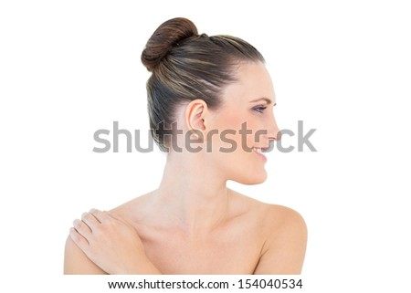 Smiling woman looking aside with hand on shoulder against white background