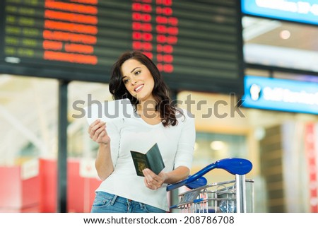 smiling woman looking at air ticket in airport - stock photo