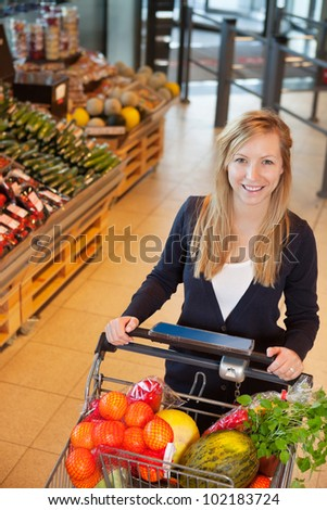 Smiling woman looking at camera while holding shopping cart in store - stock photo