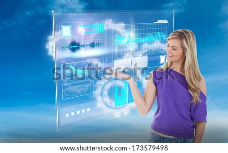 Smiling woman looking at her palm up against white cogs in the sky