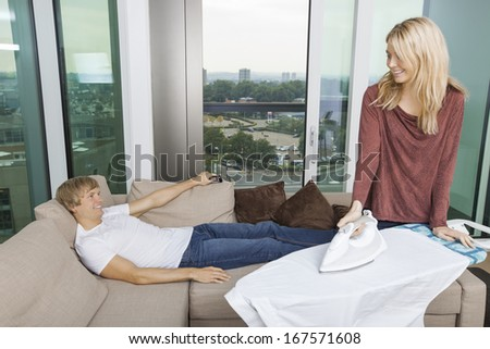 Smiling woman looking at relaxed while ironing shirt in living room at home - stock photo