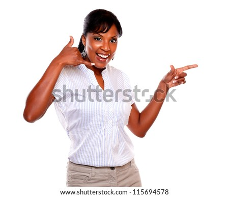 Smiling woman looking at you and pointing left while saying call me on isolated background - stock photo