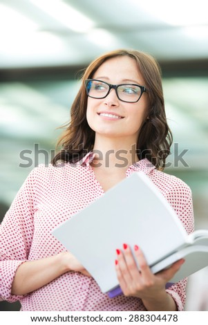 Smiling woman looking away while holding book outdoors - stock photo