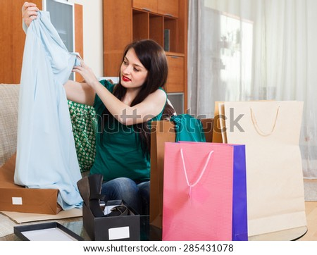Smiling woman looking dress at  home