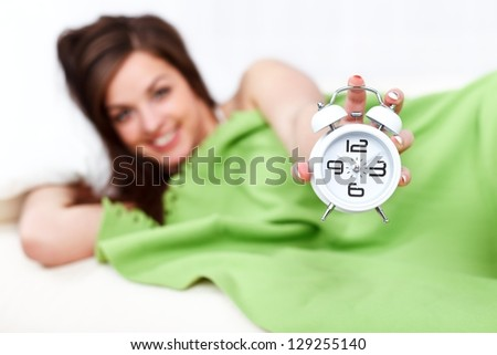 Smiling woman lying in bed holding alarm clock in hand