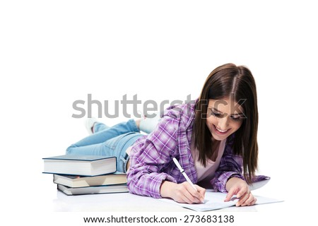 Smiling woman lying on the floor and writing in notebook over white background  - stock photo