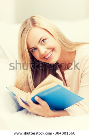 smiling woman lying on the sofa and reading book - stock photo