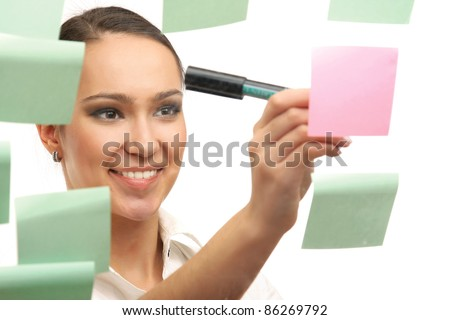 Smiling woman making notes on memo sheets isolated