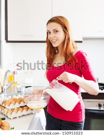 Smiling woman making scrambled eggs with milk in home