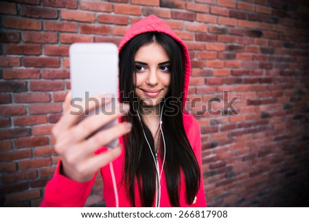 Smiling woman making selfie photo over brick wall. Looking on smartphone