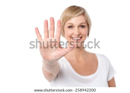 Smiling woman making stop sign with her hand - stock photo
