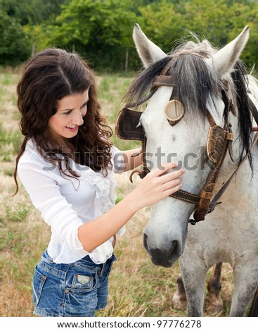 Smiling woman meeting a farm horse in a meadow - stock photo