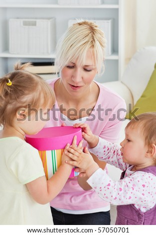 Smiling woman offering a gift to her girl in the living-room at home - stock photo