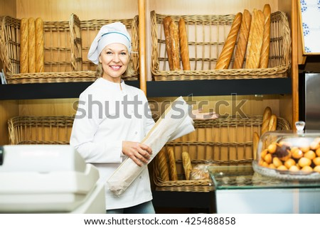 Smiling woman offering fresh and tasty bread in bakery - stock photo