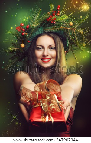 Smiling woman offering gift. Christmas magic  and lights