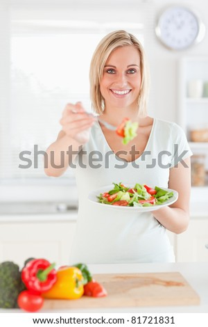 Smiling woman offering salad in the kitchen