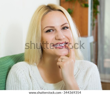 Smiling woman on couch having cunning look indoors