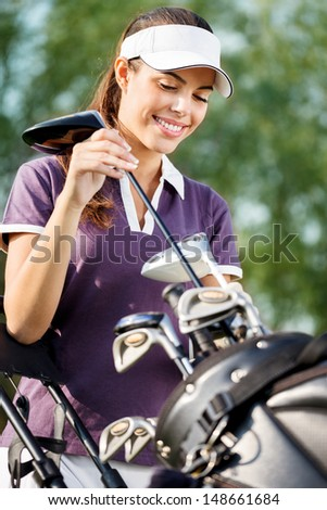 Smiling woman on golf course with golf bag