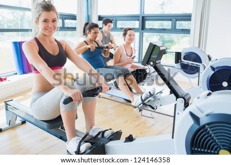 Smiling woman on rowing machine with others in fitness studio - stock photo