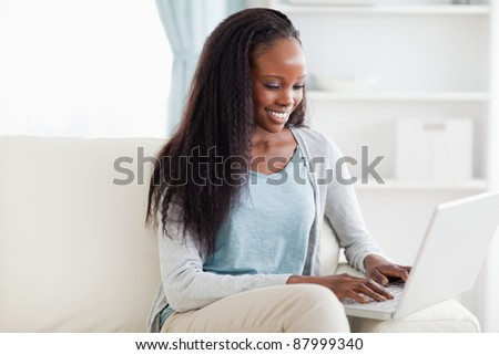 Smiling woman on sofa working on laptop