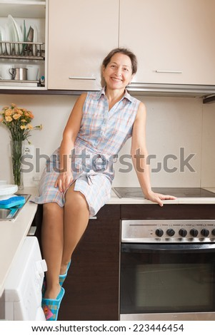 Smiling woman on table of domestic kitchen