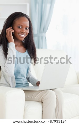 Smiling woman on the phone while working on notebook