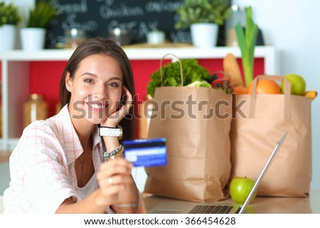 Smiling woman online shopping using tablet and credit card in kitchen - stock photo