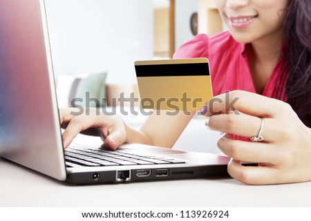 Smiling woman online shopping with laptop and a credit card, shot at home