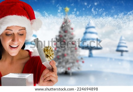 Smiling woman opening christmas present against blurry christmas scene - stock photo