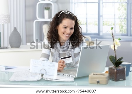 Smiling woman paying online for purchase with creditcard, using laptop computer.? - stock photo