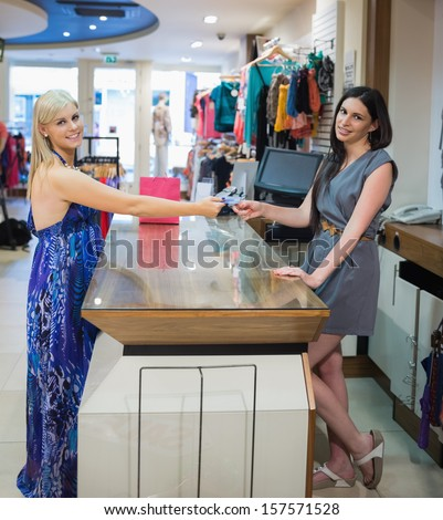 Smiling woman paying with credit card in clothing store - stock photo