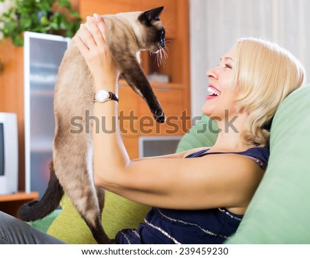 Smiling woman playing with Siamese kitten on couch at home - stock photo