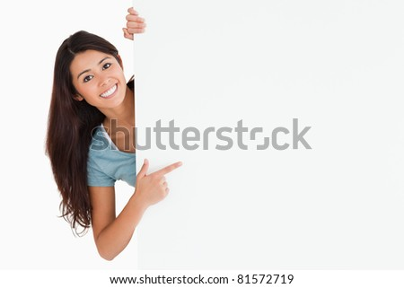Smiling woman pointing at a board while standing against a white background - stock photo